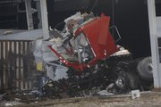 A tractor-trailer cab is wrapped around a tollbooth at the eastern terminal of the Kansas Turnpike on March 29. One person died and another is in critical condition after the truck hit the tollbooth about 3 a.m. The truck was carrying garden hoses.