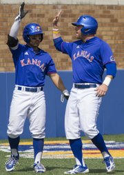 Kansas' Justin Protacio, left, and Tucker Tharp celebrate Tharp's run during the final game of Kansas' three game series against Oklahoma, Sunday afternoon at Hoglund Ballpark. The Jayhawks defeated the Sooners, 4-3, and with the victory they avoided a series sweep by Oklahoma.