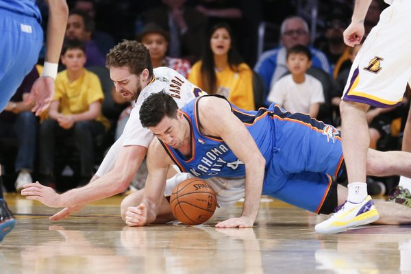 Los Angeles Lakers center Pau Gasol fights for a loose ball against Oklahoma City Thunder power forward Nick Collison during the second half of an NBA basketball game in Los Angeles, Sunday, March 9, 2014. The Lakers won 114-110. (AP Photo/Danny Moloshok)