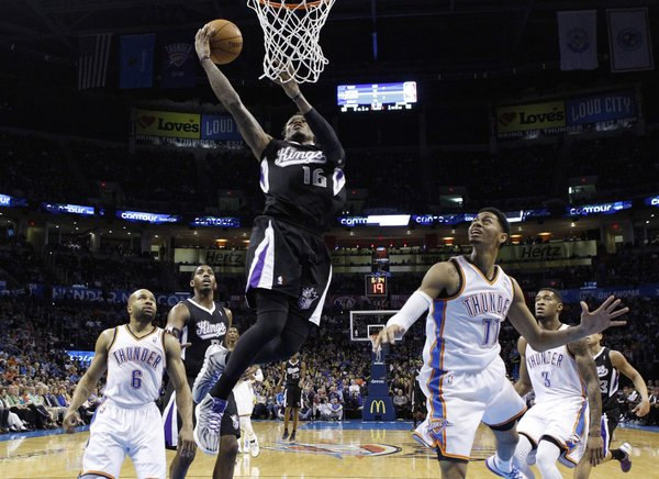 Sacramento Kings guard Ben McLemore (16) shoots between Oklahoma City Thunder guard Derek Fisher (6) and guard Jeremy Lamb (11) during the fourth quarter of an NBA basketball game in Oklahoma City, Friday, March 28, 2014. Oklahoma City won 94-81. (AP Photo/Sue Ogrocki)