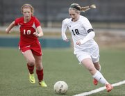 Free State midfielder Hadyn Hutchison works to save an out-of-bounds ball as she head up field past Shawnee Heights midfielder Hailey Trupp during the first half on Tuesday, April 1, 2014 at Free State High School.