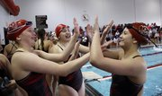 Lawrence High swimmers Mary Reed-Weston, left, Taylor Schoepf and Brittany Archer high-five after the final leg of the girls 200-yard medley relay at the Lawrence High Invitational, Tuesday at Knox Natatorium.