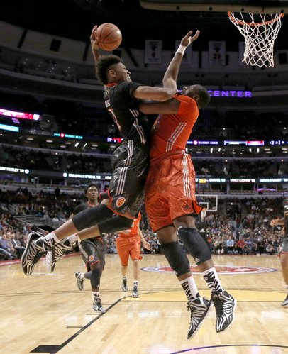 McDonald's West All-American Kelly Oubre, left, goes up for a dunk but is fouled by McDonald's East All-American Cliff Alexander during the second half of the McDonald's All-American boy's basketball game Wednesday, April 2, 2014, in Chicago . The West won 105-102.