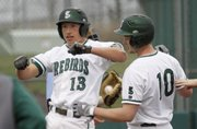 Free State senior outfielder Zach Bickling (13) jumps on home plate after a hitting a two-run home run in the bottom of the fifth inning in the Firebirds' 6-5 loss to Shawnee Mission East, Thursday at FSHS..