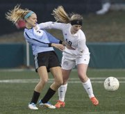 Free State soccer player Hadyn Hutchison works for position against a mid-field opponent during the Firebirds' 3-0 loss to Shawnee Mission East on Thursday, April 3, 2014, at FSHS.