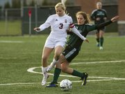 Lawrence High senior Addison Campbell (3) holds off Barstow freshman Lauren Hendrickson (5) as she makes a play on the ball during their soccer match Friday at LHS.