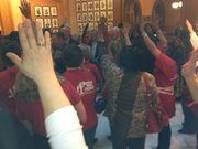 Teachers on Saturday wave `hello' as legislators leave the House chamber. The teachers were protesting a plan to repeal teacher tenure laws.