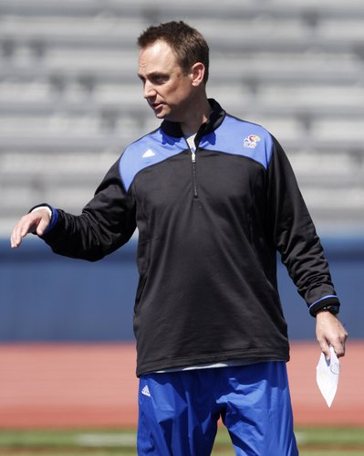 Kansas wide receiver coach Eric Kiesau participates in drills during a KU football practice Saturday, April 5, 2014, at Memorial Stadium.