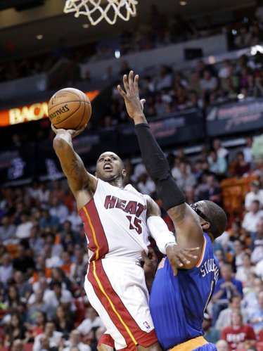 Miami Heat guard Mario Chalmers (15) goes up for a shot against New York Knicks forward Amar'e Stoudemire (1) during the first half of an NBA basketball game, Sunday, April 6, 2014, in Miami. (AP Photo/Wilfredo Lee)