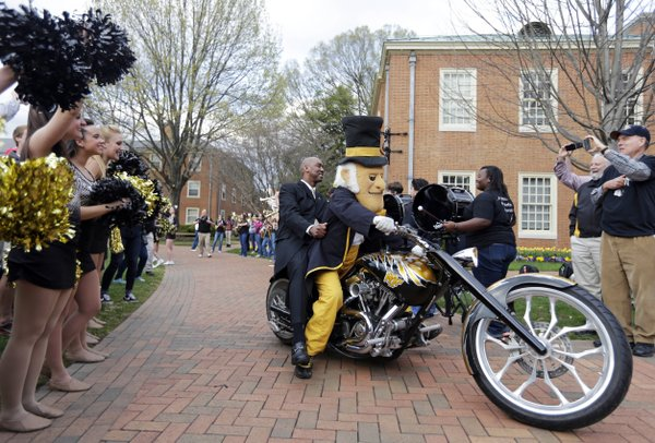 Newly hired Wake Forest head basketball coach Danny Manning rides on the back of a motorcycle driven by the team mascot as he is introduced to students and supporters at a rally at the school in Winston-Salem, N.C., Tuesday, April 8, 2014. The former Kansas star is taking over the project of rebuilding the Demon Deacons. (AP Photo/Chuck Burton)