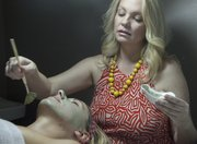 Karin Kelley, of Karin Kelley Skin Care, 3211 Wakarusa Drive, applies a French green clay detoxification mask on a client.