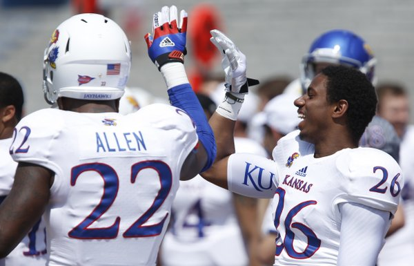 White Team defenders Greg Allen and Brandon Hollomon celebrate a stop by the White Team during the first half of the Kansas Spring Game on Saturday, April 12, 2014 at Memorial Stadium. Nick Krug/Journal-World Photo