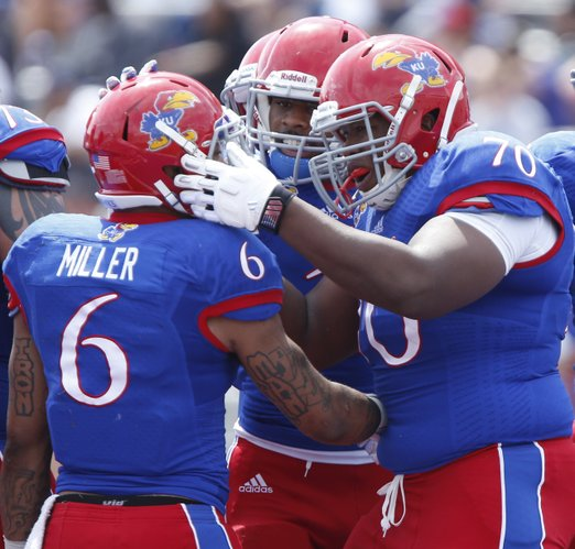 Blue Team offensive lineman Keyon Haughton (70) gives a slap on the helmet to running back Darrian Miller after Miller's second-half touchdown against the White Team during he Kansas Spring Game on Saturday, April 12, 2014 at Memorial Stadium. Also pictured is receiver Rodriguez Coleman, back. Nick Krug/Journal-World Photo