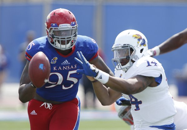 White Team quarterback Michael Cummings pitches the ball to a teammate as Blue Team defensive lineman Andrew Bolton closes in during the second half of the Kansas Spring Game on Saturday, April 12, 2014 at Memorial Stadium. Nick Krug/Journal-World Photo