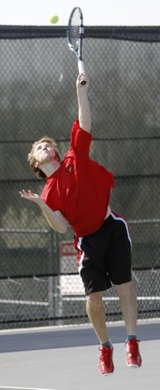 Lawrence High tennis player Thomas Irick serves during his No. 1 doubles tennis match against Free State in the City Showdown on Tuesday, April 15, 2014, at FSHS.