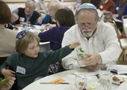 Mike Yoder/Journal-World Photo.Jakob Rudnick, left, with the help of Steve Hurst, Perry, dips a sprig of parsley in a glass of salt water during the the Passover Seder Tuesday, April 15, 2014, at Lawrence Jewish Community Congregation. The Seder ritual included telling the story of liberation of the Israelites from slavery, discussing the story, eating matza, partaking of symbolic foods placed on the Passover Seder Plate, and the celebration of freedom.