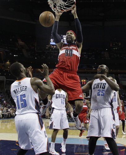 Washington Wizards' Drew Gooden (90) dunks as Charlotte Bobcats' Kemba Walker (15) and Al Jefferson (25) watch during the second half of an NBA basketball game in Charlotte, N.C., Monday, March 31, 2014. The Bobcats won 100-94. (AP Photo/Chuck Burton)