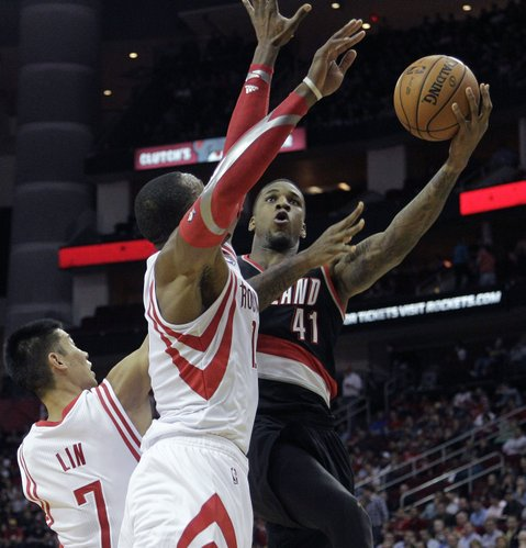 Portland Trail Blazers forward Thomas Robinson (41) drives to the basket past Houston Rockets' Dwight Howard (12) and Jeremy Lin (7) during the first half of an NBA basketball game, Monday, Jan. 20, 2014, in Houston. (AP Photo/Bob Levey)