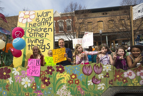A trailer decorated with painted flowers pulls parade participants down Massachusetts Street during the annual Earth Day parade in 2014.