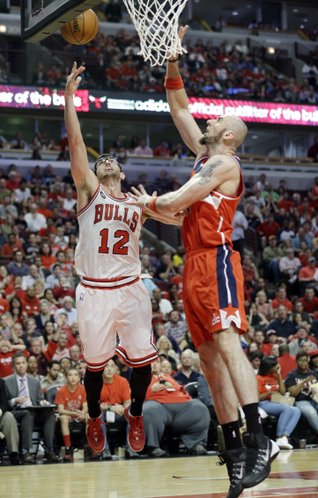 Chicago Bulls guard Kirk Hinrich, left, shoots against Washington Wizards center Marcin Gortat during the second half in Game 1 of an opening-round NBA basketball playoff series in Chicago, Sunday, April 20, 2014. The Wizards won 102-93. (AP Photo/Nam Y. Huh)