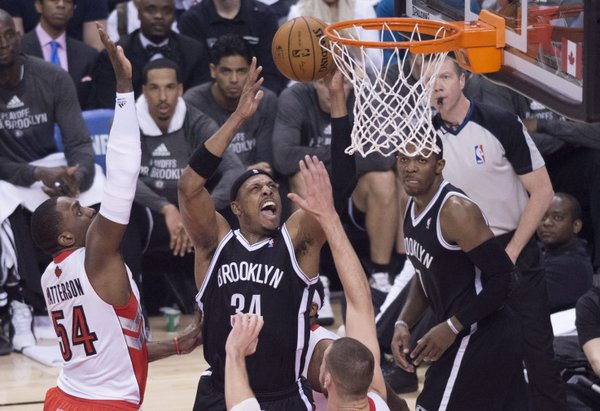 Brooklyn Nets' Paul Pierce, center, drives to the net against Toronto Raptors Patrick Patterson, left, during the first half of Game 1 of an opening-round NBA basketball playoff series, in Toronto on Saturday, April 19, 2014. (AP Photo/The Canadian Press, Darren Calabrese)