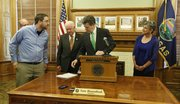 Governor Sam Brownback looks at a petition delivered by Aaron Estabrook, front left, a school board member from Manhattan, Kan., before signing a school finance bill that will increase funding to schools but which also contains some controversial policy changes, Monday, April 21, 2014 in his ceremonial office at the Kansas Statehouse in Topeka, Kan. With Brownback are House Appropriations chairman Gene Suellentrop, left and partially obscured, R-Wichita, House Speaker Ray Merrick, R-Stillwell and Senate President Susan Wagle, R-Wichita. Estabrook had asked Brownback not to sign the bill, which has been criticized by teacher groups because it repeals tenure for teachers.