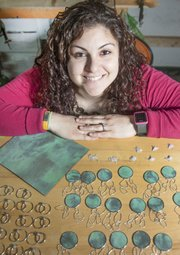 Britta McKee, a Kansas University graduate, is one of a handful of artists who are creating  jewelry from old pieces of the Kansas Statehouse dome. McKee takes larger sections of the copper and cuts out small pieces to shape into rings, earrings and other jewelry.