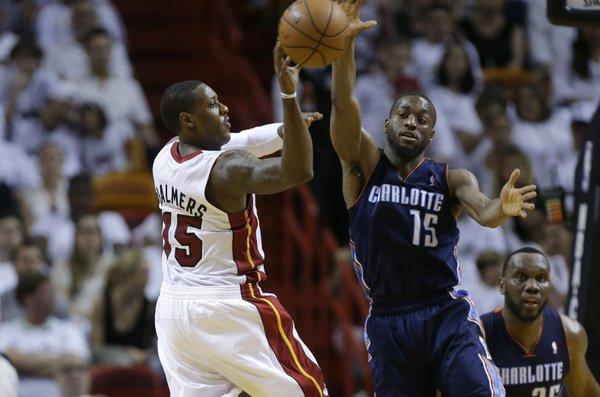Miami Heat's Mario Chalmers (15) passes the ball as Charlotte Bobcats' Kemba Walker (15) defends during the second half in Game 1 of an opening-round NBA basketball playoff series, Sunday, April 20, 2014, in Miami. The Heat defeated the Bobcats 99-88. (AP Photo/Lynne Sladky)