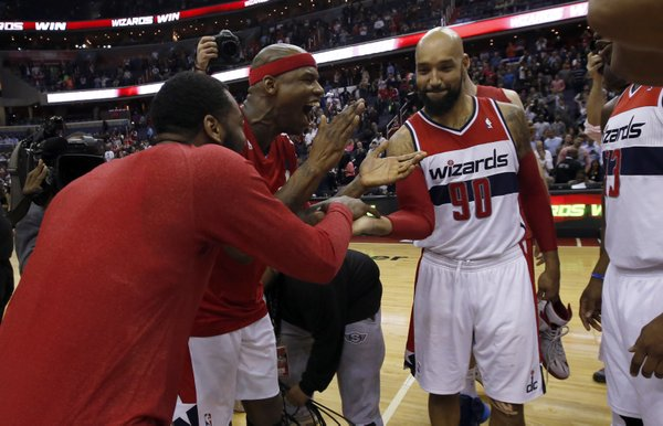 Washington Wizards John Wall, left, celebrates with Al Harrington and Drew Gooden (90) after an NBA basketball game against the Boston Celtics Wednesday, April 2, 2014 in Washington. The Wizards won 118-92, and clinched a playoff berth. (AP Photo/Alex Brandon)