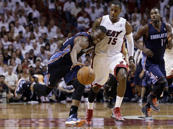 Charlotte Bobcats' Kemba Walker, left, tries to gain control of the ball as Miami Heat's Mario Chalmers (15) defends during the second half in Game 2 of an opening-round NBA basketball playoff series, Wednesday, April 23, 2014, in Miami. The Heat defeated the Bobcats 101-97. (AP Photo/Lynne Sladky)