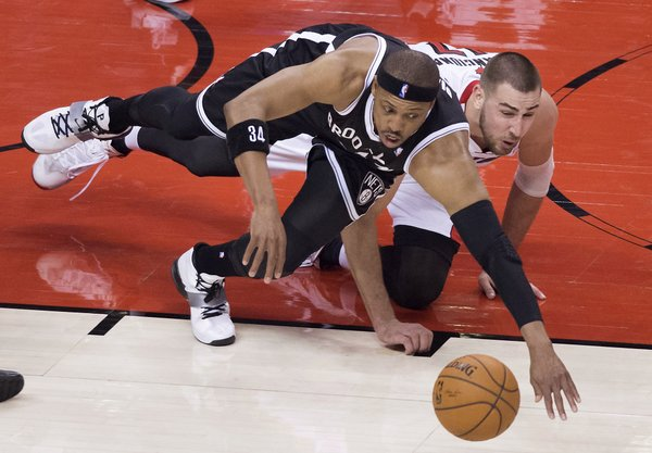Brooklyn Nets' Paul Pierce, left, and Toronto Raptors' Jonas Valanciunas dive for the ball during the first half of Game 1 of an opening-round NBA basketball playoff series, in Toronto on Saturday, April 19, 2014. (AP Photo/The Canadian Press, Darren Calabrese)