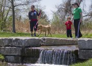 From left, Eunice Del Rossario and her friend's dog, April, spend time outdoors with, Sean Melchert, 3, and his mother, Sarah, at the Rotary Arboretum, 5100 W. 27th St., on Friday. Lawrence has many parks, trails and nature centers where people can do outdoor activities this spring.