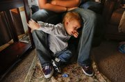 Eighteen-month-old Braxton Bottoms plays under his mother, Brandi, on a recent day in their Eudora home. In October, Brandi noticed burns on Braxton after picking him up from an unlicensed day care provider in Eudora.