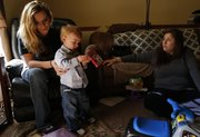 Eudora resident Brandi Bottoms, left, talks with Mandy Gwirtz, a social worker with the Lawrence-Douglas County Health Department's Healthy Families program, during a recent home visit. With Brandi is her 18-month-old son Braxton. In October, Bottoms noticed burns on Braxton after picking him up from an unlicensed day care provider in Eudora.
