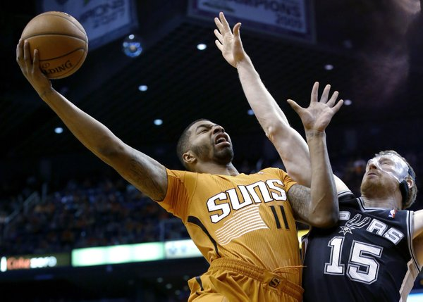 Phoenix Suns' Markieff Morris (11) tries to get off a shot over San Antonio Spurs' Matt Bonner (15) during the first half of an NBA basketball game, Friday, Feb. 21, 2014, in Phoenix. (AP Photo/Ross D. Franklin)