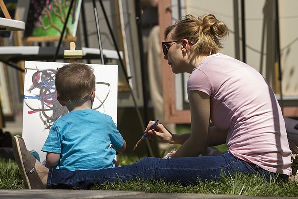 Sara Ziegler, of St. Louis, Mo., helps her nephew, two-year-old Elliot Polson, of Lawrence, make his own art in the park during the 53rd annual Art in the Park event, held Sunday, May 4, 2014, at South Park in downtown Lawrence.