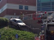 Lawrence-Douglas County Fire Medical personnel attempt to remove a car from a staircase behind Joseph R. Person Hall on Kansas University campus Monday afternoon. A man allegedly led police on a short car chase, which ended with him impaling his vehicle on the staircase railing.