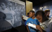 Mecca Cameron, a fifth-grader at McEachron Elementary School in Topeka, examines a historic photo showing Elizabeth Eckford, far left, attempting to enter a high school in Little Rock, Ark., on Sept. 4, 1957. Mecca and Kamarion Smith, right, and other students toured the Brown v. Board of Education National Historic Site on Monday in Topeka.