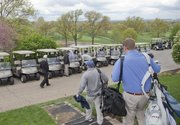 Golfers head to their carts for men's guest day last week at the Lawrence Country Club. The club is celebrating its 100th anniversary this year.