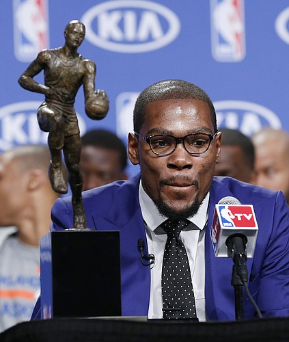Oklahoma City Thunder's Kevin Durant is pictured with the MVP trophy during the news conference to announce that Durant is the winner of the 2013-14 Kia NBA Basketball Most Value Player Award in Oklahoma City, Tuesday, May 6, 2014. (AP Photo/Sue Ogrocki)