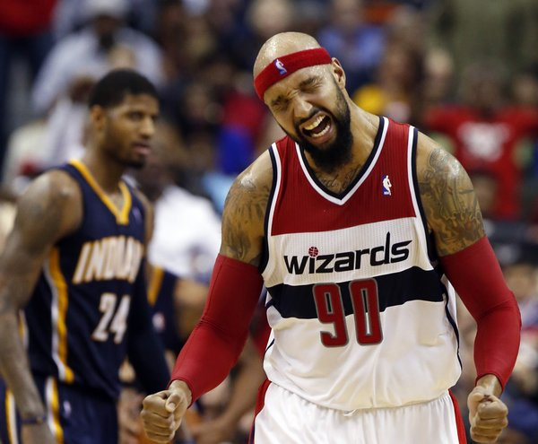 Washington Wizards forward Drew Gooden (90) celebrates after a play with Indiana Pacers forward Paul George (24) nearby in the second half of an NBA basketball game on Friday, March 28, 2014, in Washington. The Wizards won 91-78. (AP Photo/Alex Brandon)