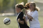 Lawrence High's Micaela Riley collides with Shawnee Mission Northwest's Alix Willming going for the ball during the first half, Tuesday, May 6, 2014 at Lawrence High School.
