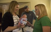 Nurse midwife Karen Honn visits with new parents Ryan and Rebekah Cantrell and their baby, Savannah, at Lawrence Memorial Hospital earlier this month. The Cantrells, of Lawrence, used a midwife to have a natural birth. Midwives are increasing in popularity in Lawrence and across the nation.