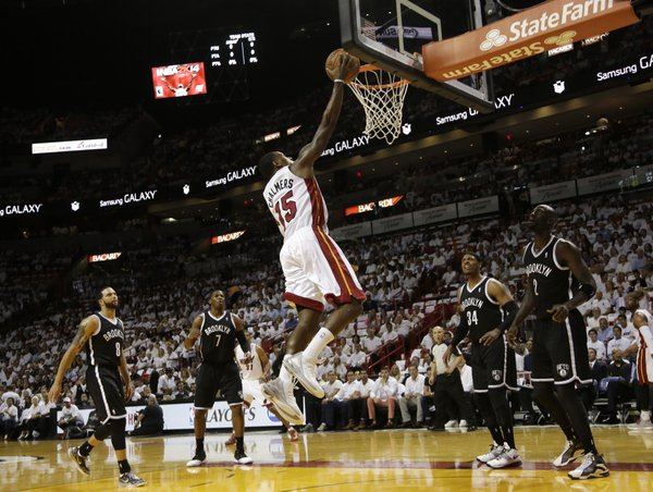 Miami Heat's Mario Chalmers (15) shoots over Brooklyn Nets' Deron Williams (8), Joe Johnson (7), Paul Pierce (34) and Kevin Garnett (2) in the first half of Game 1 in an Eastern Conference semifinal basketball game, Tuesday, May 6, 2014, in Miami. (AP Photo/Lynne Sladky)