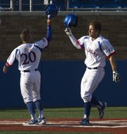 Kansas junior Michael Suiter, right, taps helmets with teammate Justin Protacio over home plate after Suiter's two-run home run brought them both around the bases for scores during Kansas' game against West Virginia, Friday evening at Hoglund Ballpark. The Jayhawks defeated the Mountaineers, 5-3. The two teams will continue the series tomorrow, with the first pitch scheduled for 2 p.m.