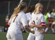 Lawrence High senior Addison Campbell (3) flashes a smile while being congratulated by teammates after scoring during their soccer match, played Wednesday at LHS.