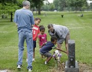 Owen Thompson, 6, center, touches the gravestone of his grandfather Lawrence Turner, a veteran of World War II, during a visit to Oak Hill Cemetery before the family attended the American Legion Liberty-Post No. 14 Memorial Day services Monday. Joining Owen from left is his grandfather Bill Gillispie, his brother Turner, 9, sister Evelyn, 3 and mother, Jessica Thompson, of Blue Springs, Mo.