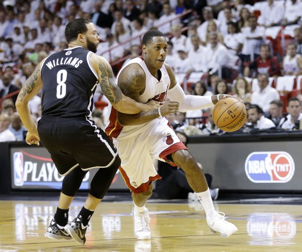 Miami Heat guard Mario Chalmers drives past Brooklyn Nets guard Deron Williams (8) during the first half of Game 2 of an Eastern Conference semifinal basketball game, Thursday, May 8, 2014 in Miami. (AP Photo/Wilfredo Lee)