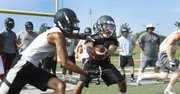Free State senior Carson Bowen, left, takes the ball from sophomore Zach Sanders during Free State summer football camp, Tuesday, June 3, 2014, at FSHS.