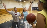 From left, Free State High assistant girls basketball coach Kevin Riley shows senior Hannah Shoemaker how to defend the paint at camp Wednesday, June 4, 2014, at Southwest Middle School.